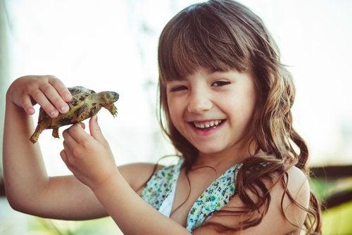 Niña con una tortuga de la mano representado la técnica de la tortuga.