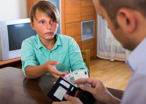 Niño recibiendo una paga semanal como parte de las actividades de educación financiera.