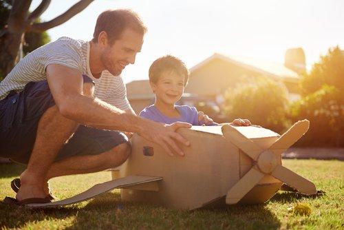 Padre e hijo con el avión de juguete hecho de cartón.