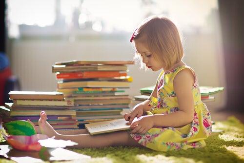 Niña sentada en una alfombra lee libros