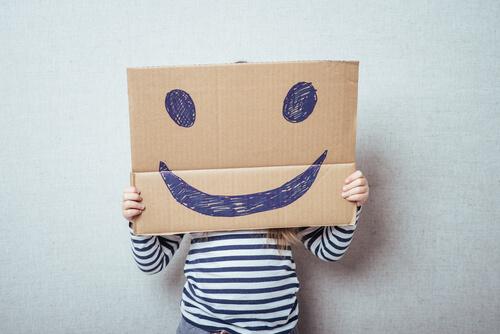 Niño con un cartel en el que hay una cara sonriendo