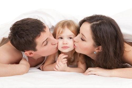 Padres dándole muchos besos a su hija.