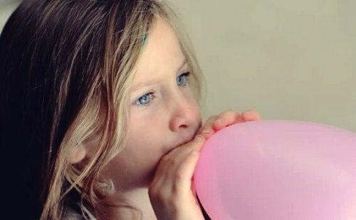 Niña hinchando un globo para jugar a alguno de los juegos para pasar un día de verano en casa.