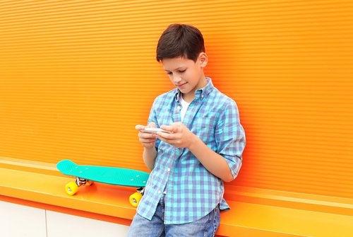 Niño con el teléfonos jugando a apps infantiles para aprender matemáticas.