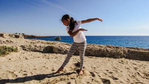 Niña haciendo danza en la playa.