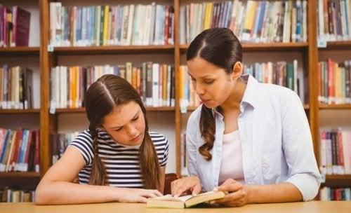 Niña mejorando la atención en el aprendizaje con su madre en la biblioteca.