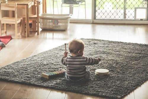 Bebé sentado en una alfombra tocando un xilófono y una pandereta.