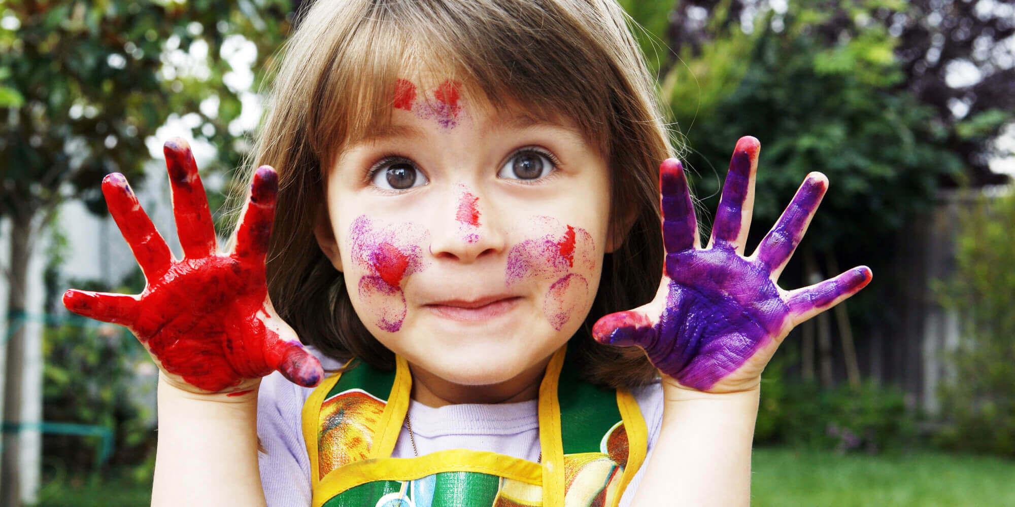 Niña soportando el aburrimiento desarrollando su creatividad pintando con las manos.