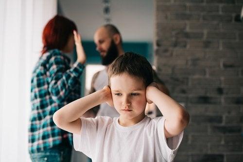 Niño tapándose los oídos mientras sus padres discuten por el divorcio.