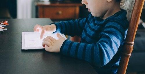 Niño jugando con una tablet en casa.