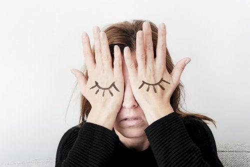 Mujer con las manos en los ojos. En ellas tiene pintadas unas pestañas simulando los ojos.