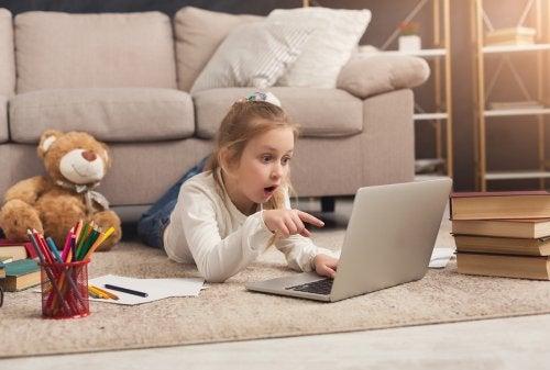 Niña con el ordenador con una expresión de asombro tras descubrir algo nuevo.