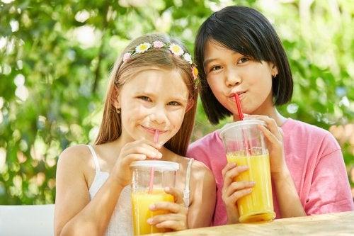 Niña bebiendo un zumo, que no equivale a una pieza de fruta, como señalan los mitos sobre la fruta.
