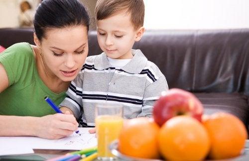 Madre e hijo haciendo las tareas escolares en el salón.
