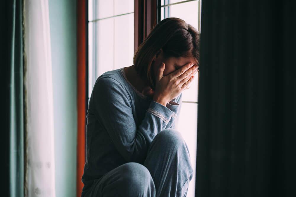 Mujer triste sentada en una ventana