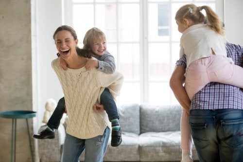 Padres jugando con sus hijos para incrementar su sentido del humor.