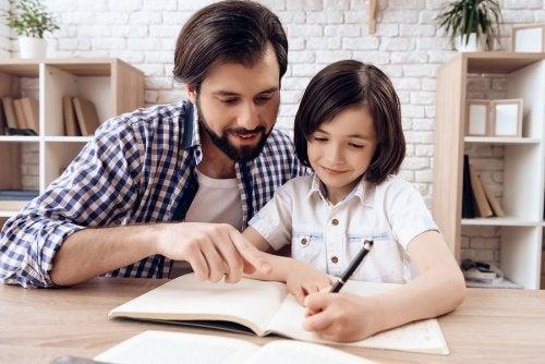 Padre ayudando a su hijo con los deberes en un buen espacio en casa.