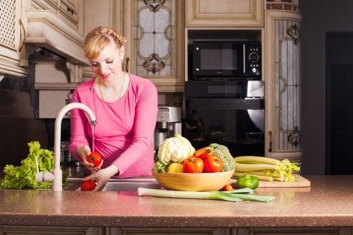 Mujer embarazada lavando frutas y verduras para tener una buena salud digestiva gracias a su alimentación.