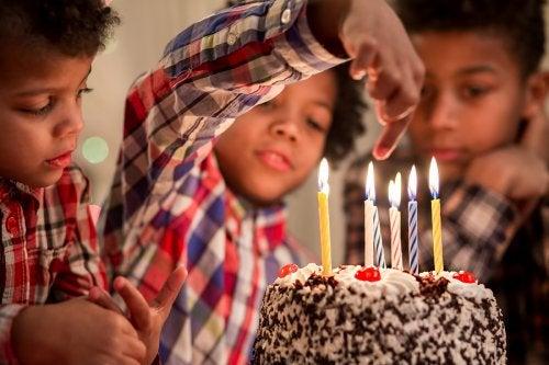 Niño cumpliendo siete años. Tiene una tarta delante con velas.