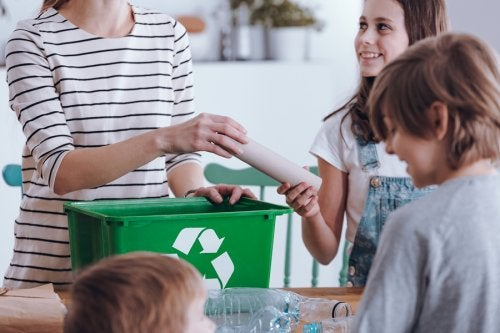 Niños reciclando en casa con ayuda de su madre.