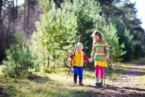 Niños dando un paseo por el bosque para conocer más la naturaleza después de haber leído los libros de la colección ¿Por qué debo...?