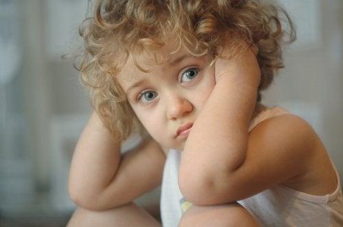 Niño triste porque tiene que dejar de jugar y sus padres no son capaces de validar sus emociones.