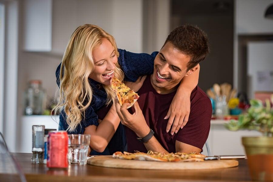 Una pareja muy feliz come pizza.