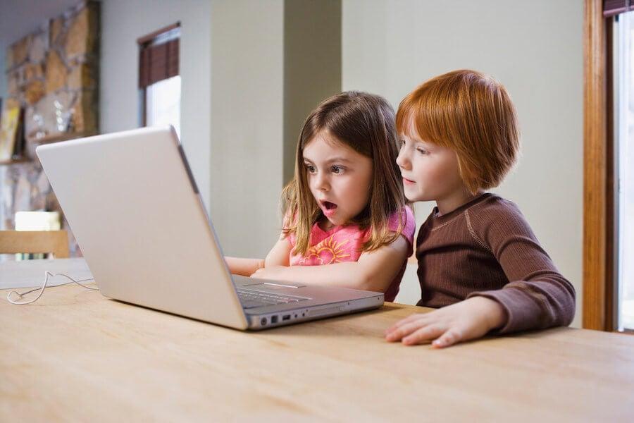 Niños emprendedores navegando por Internet con un ordenador.