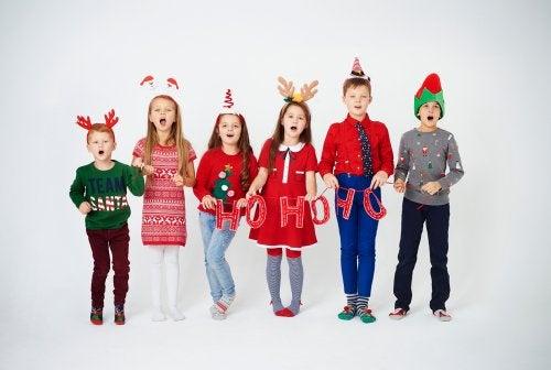 Niños cantando villancicos con adornos de Navidad.