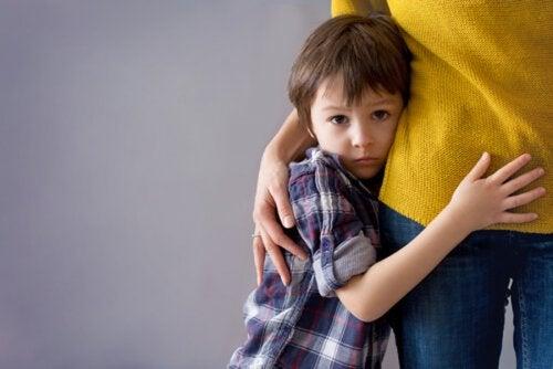 Niño con mucha timidez abrazado a su madre.