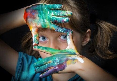 Niña con las manos llenas de pintura tras leer algunos libros de arte para niños.