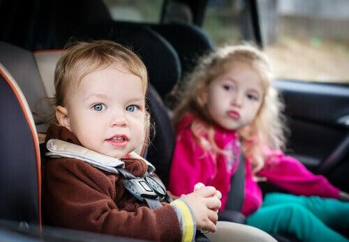 Dos niños sentados en las sillas del coche.