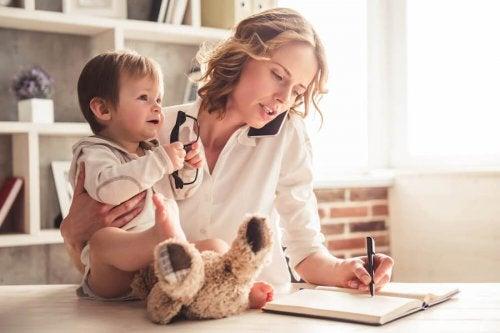 Madre con su hijo trabajando en casa por la autoexigencia en la maternidad.