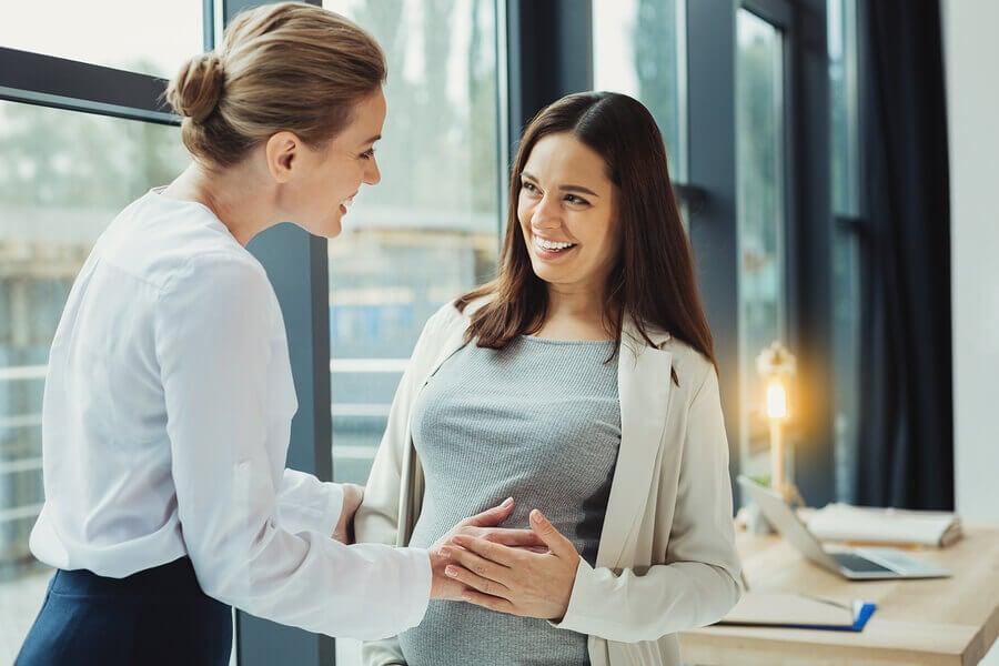 Jefa animando a su empleada embarazada.
