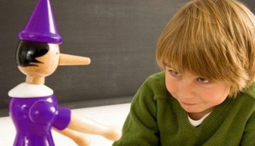 Niño con un muñeco de madera con la nariz larga por decir mentiras.