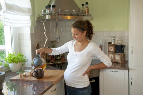 Mujer embarazada en la cocina de su casa haciéndose una infusión.