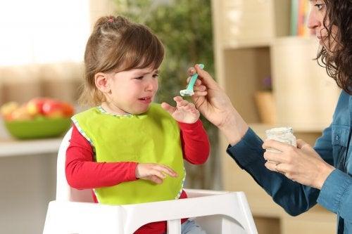 Niña rechazando la comida debido al trastorno de alimentación selectiva en la infancia.