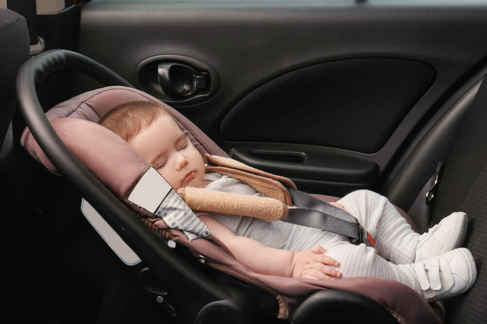 Bebé dormido en la silla del coche.