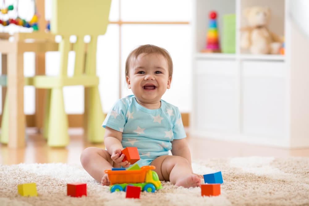 Bebé jugando en el suelo de casa muy sonriente.