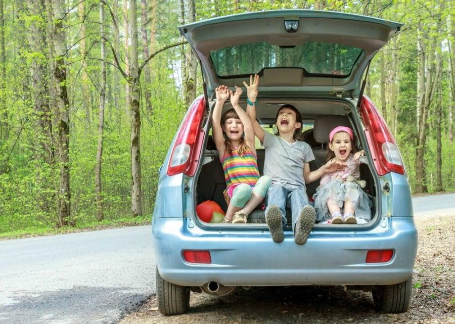 Tres niños muy contentos sentado en el maletero abierto de su coche para familias numerosas.