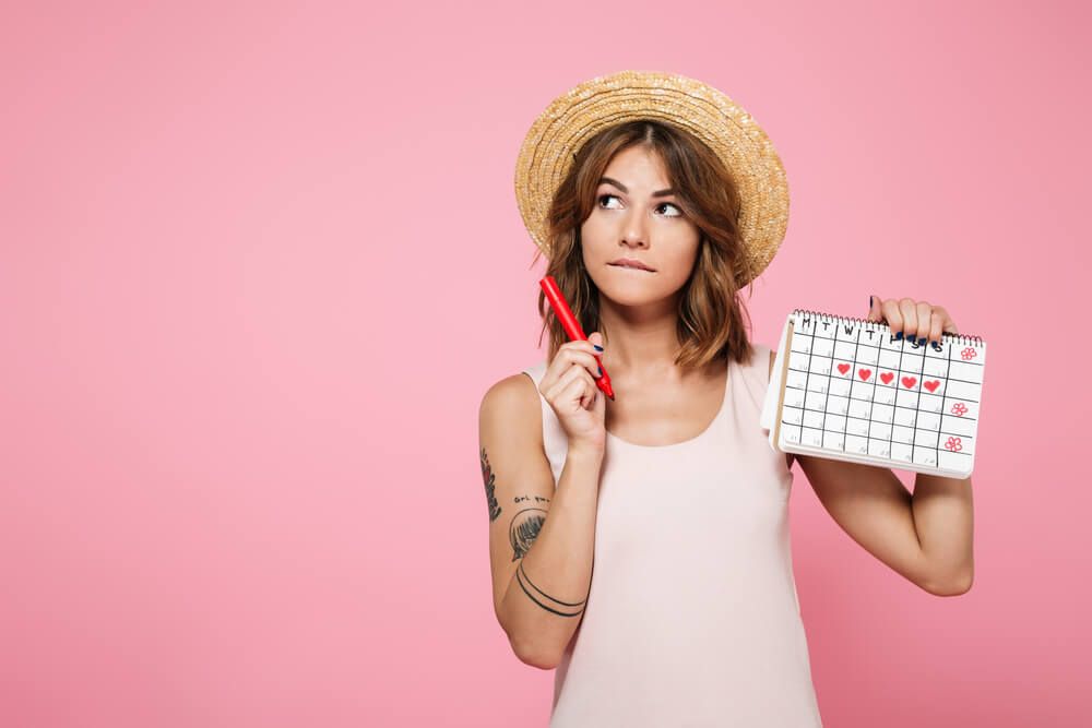 Une femme qui examine son calendrier menstruel.