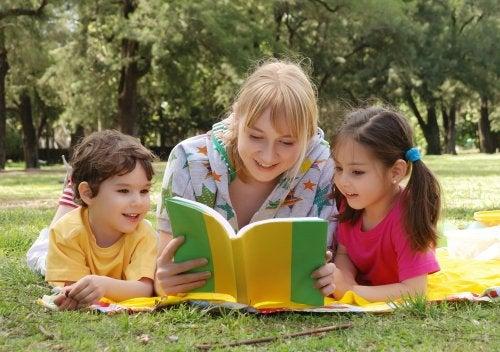 Una mamá lee un libro sobre las emociones a su hijo y a su hija. Están los tres tumbados en un parque.