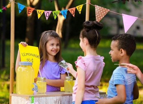 Niña vendiendo limonada en un puesto como parte de las actividades de educación financiera.