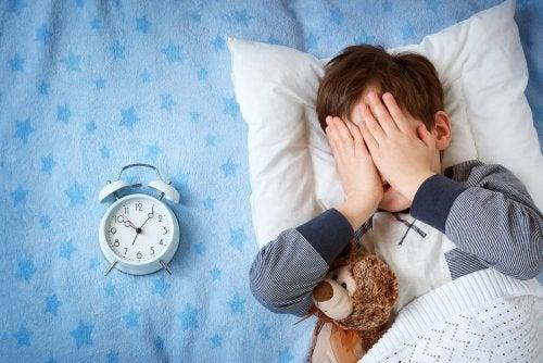 Niño sin descanso en su cama.
