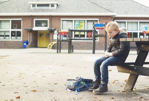 Niño sentado solo en el patio del colegio.