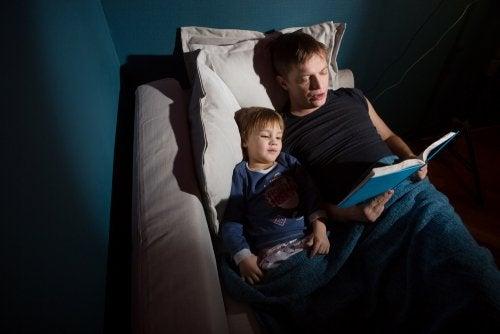 Un padre lee a su hijo cuentos de miedo en penumbra.