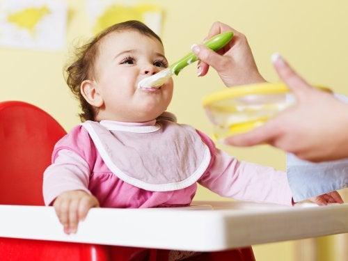 Bebé comiendo con su madre, quien está realizando la introducción de los alimentos de manera adecuada.