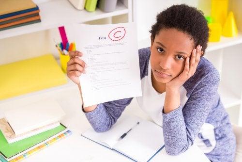 Chica adolescente con un examen con mala nota en las manos.