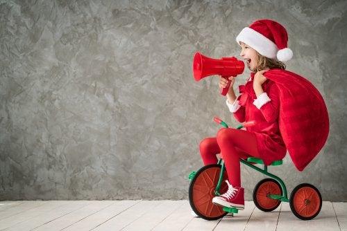 Niña disfrazada de Papá Noel pregonando algunas de las frases navideñas que proponemos.