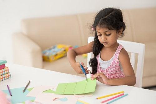 Niña recortando un papel para pasar el aburrimiento y fomentar su creatividad.